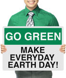 Earth Day Everyday. A man holding a sign with an environmental message Royalty Free Stock Image