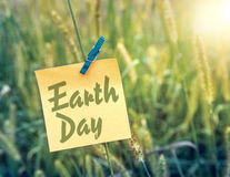 Earth Day. On a sticky note in a green field Stock Image