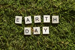 Earth day written with wooden letters cubed shape on the green grass. royalty free stock images