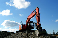 Earth digging excavator. A large excavator sitting on top of a pile Royalty Free Stock Photo