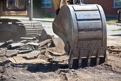 Earth digging Machine. The bucket of a earth mover digging machine as it is about to dig into the earth stock photo