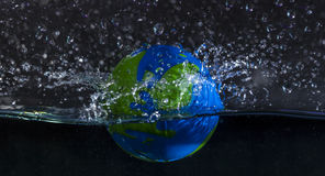 Earth dropped in water Stock Photo