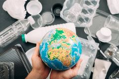 Earth drowned plastic garbage globe people hands. Earth drowned in plastic garbage. Closeup of globe in human hands. Ecology problem stock photo