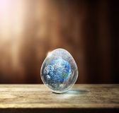 Earth in the egg. Planet earth inside an egg. Elements provided by nasa Stock Photos