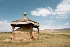 Earth embankment installed as a monument in the valley between the mountains of Central Asia Stock Photo