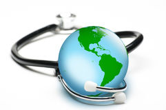 Earth enclosed by stethoscope. Concept for world healthcare, looking after the planet. Isolated on white. Focus on globe Royalty Free Stock Photo