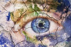 Earth extinction concept. Close up image of woman face with earth painted cracked texture with iris earth. Creative. Earth extinction concept. Close up image of stock photo