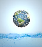 Earth falling into water Royalty Free Stock Images