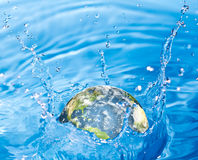 Earth falling into water Royalty Free Stock Image