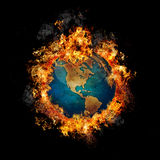 Earth on Fire. Glassy Earth with realistic texture and flames on black background Royalty Free Stock Images