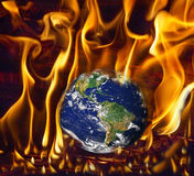 Earth on fire. Earth globe scorched in fire symbolizing global warming stock photography