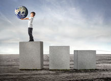 Earth at first place. Child standing on the highest of three cubes and holding the earth in his hands stock image