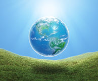 Earth floating over grass Stock Images