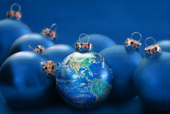 Earth globe as christmas ball between blue baubles, metaphor uni. Earth globe as christmas ball between blue baubles, metaphor for universal peace or Royalty Free Stock Images