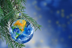 Earth globe as a Christmas bauble on fir branch, copy space. Earth globe as a Christmas bauble on fir branch of a christmas tree, Merry Christmas all over the stock photo