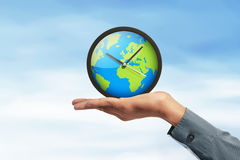 Earth globe clock in human hands Royalty Free Stock Photography