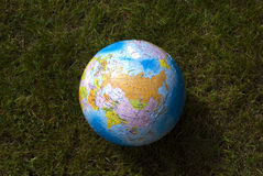 Earth globe in the grass Royalty Free Stock Images