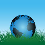 Earth Globe in Green Grass. An Earth globe, displaying the Atlantic and continentes, in a field of green grass under a blue sky stock illustration