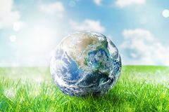 Earth globe in a green pristine field. World provided by NASA stock image