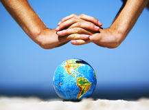 Earth globe with hands over it. Conceptual image Royalty Free Stock Photo