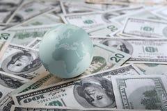Earth globe on heap of money Stock Photo