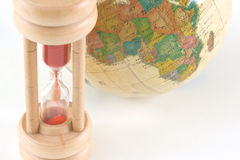 Earth globe and hour glass. Earth globe and wooden hour glass royalty free stock photo
