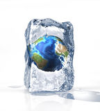 Earth globe into an ice brick on a white surface. Earth globe into an ice brick standing on a white surface, with some water pool. On white background Royalty Free Stock Images