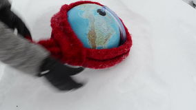 Earth globe lie winter snowbank hand gloves put scarf stock video footage