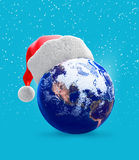 Earth globe and santa hat Royalty Free Stock Images