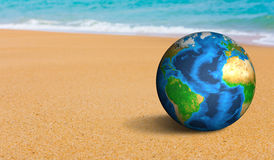 Earth globe on the sea beach (Elements of this image furnished b Stock Photography