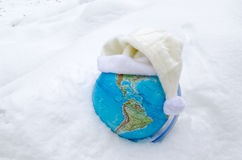 Earth globe sphere snow snowbank white cap concept. Earth globe sphere in winter snow snowbank and white cap hat on it concept royalty free stock image