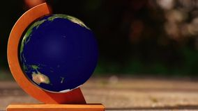 Spinning Earth globe. Earth globe spinning on orange axis on tabletop stock video