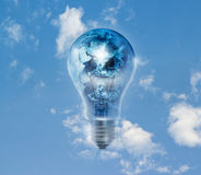 Earth globe and storm in the light bulb on a blue sky vibrant Stock Photography