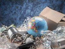 Earth globe on trash heap. Earth globe dumped onto trash heap - global environmental pollution concept Royalty Free Stock Photography