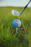 Earth Golf. A miniature globe on a tee at a golf course. A golf club is poised behind the globe ready to swing stock photos