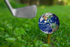 Earth on golf tee. From the ground level with grass and puttter royalty free stock photo