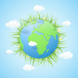 Earth with grass and clouds on blue background Royalty Free Stock Images