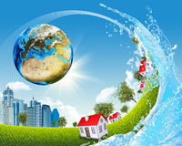 Earth, green grass, buildings and water Stock Photo