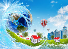 Earth, green grass, buildings and water Stock Photography
