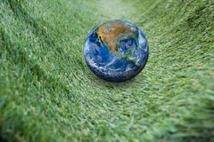 The earth on green grass, including elements furnished by NASA. Earth on green grass, including elements furnished by NASA Stock Image