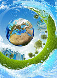 Earth, green grass, skyscrapers and water Stock Photography