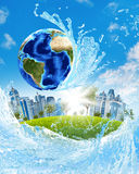 Earth, green grass, skyscrapers and water Royalty Free Stock Photos
