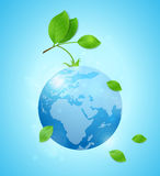Earth and green leaves. Planet Earth and green leaves on a blue background. Card for Earth Day Royalty Free Stock Image