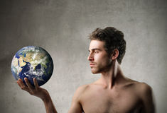 Earth in a hand. Handsome man holding the earth in his hand stock image