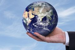 Earth in a hand 2. Earth in a hand on background blue sky Royalty Free Stock Image