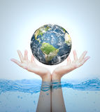 Earth in hand over water Royalty Free Stock Image
