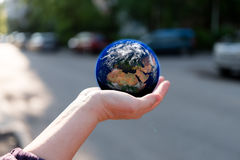 Earth in hand. A person holding the Earth in her hands with streets and parked cars on the background. Earth textures courtesy of NASA/JPL-Caltech Stock Photography