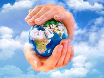 Earth in hands. With clouds on the sky Royalty Free Stock Image