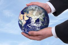 Earth in a hands, blue. Earth in a hands on background blue sky Royalty Free Stock Image