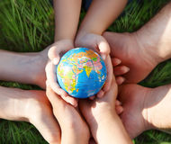 Earth in hands of the family Royalty Free Stock Photos